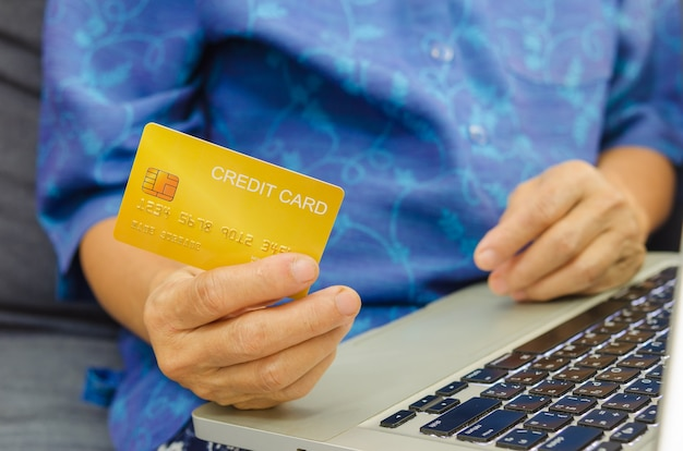 Mulher sênior segurando cartões de crédito no laptop