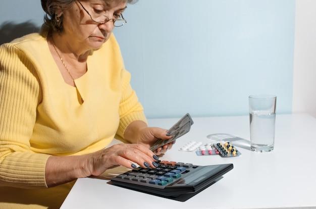 Mulher sênior segurando dinheiro e contando com a calculadora. pensionista sentado na cozinha com medicamentos. conceito de depressão, preço do medicamento, custo do tratamento