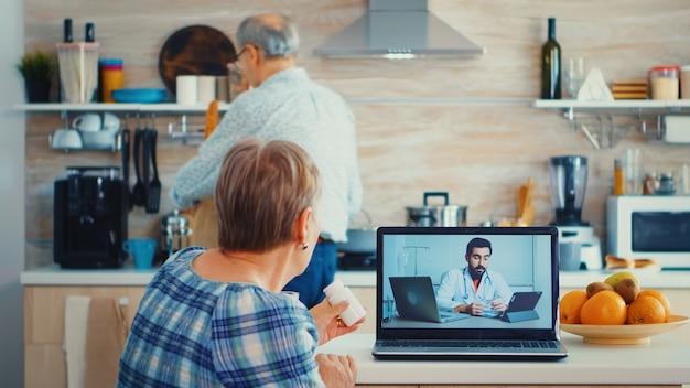 Mulher sênior, segurando o frasco de comprimidos durante a videoconferência com o médico, usando o laptop na cozinha. consulta de saúde online para idosos, drogas, conselhos sobre doenças, telemedicina médica
