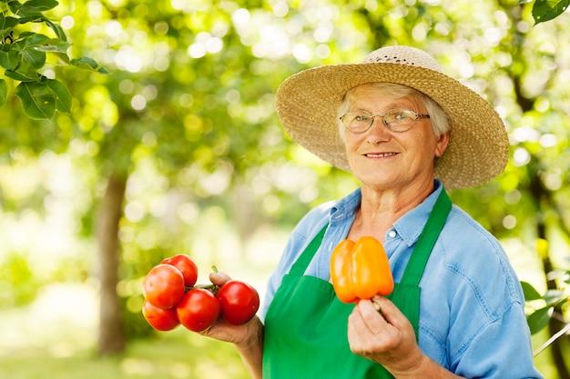 Mulher sênior segurando tomates e pimentão amarelo