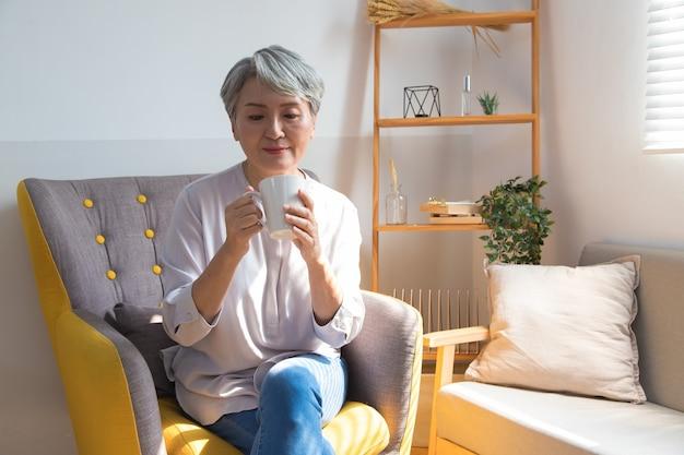 Mulher sênior segurando uma xícara de café ou chá relaxante em casa pela manhã.