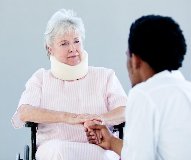 Mulher sênior sentada em uma cadeira de rodas com uma cinta de pescoço falando com seu médico