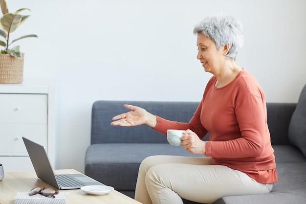 Mulher sênior sentada no sofá tomando café e dando uma conferência on-line no laptop em casa