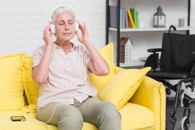 Mulher sênior, sentado na música escuta sofá amarelo no fone de ouvido