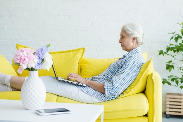 Mulher sênior, sentar sofá, usando computador portátil