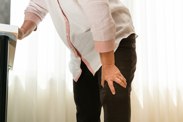 Mulher sênior, sofrimento, de, joelho, dor, casa, conceito problema saúde