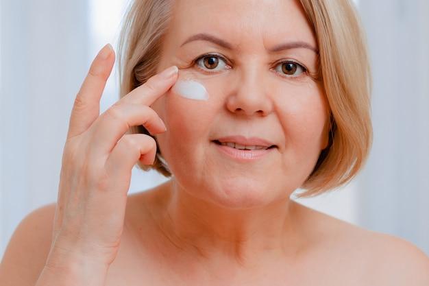 Mulher sênior sorridente, aplicar a loção antienvelhecimento para remover as olheiras sob os olhos.