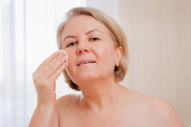 Mulher sênior sorridente, aplicar loção antienvelhecimento para remover olheiras sob os olhos.
