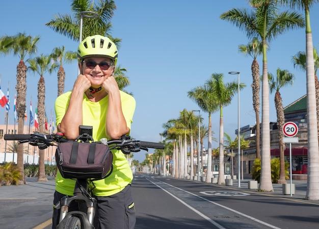Mulher sênior sorridente, ativa, com óculos e capacete amarelo, andando de bicicleta em uma estrada deserta
