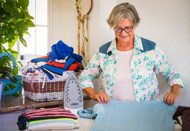Mulher sênior sorridente atraente passando roupa em casa