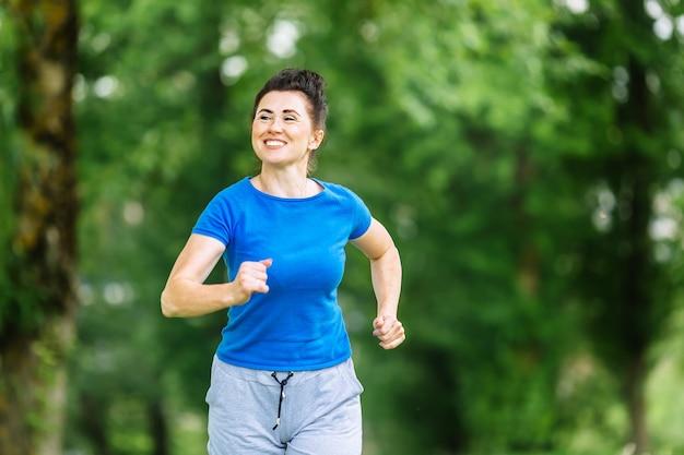 Mulher senior sorridente correndo no parque