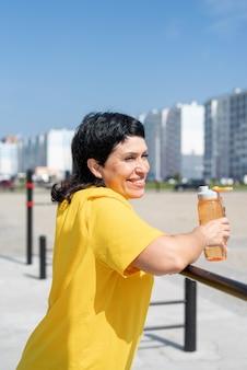 Mulher sênior sorridente descansando após o treino ao ar livre nas barras do campo esportivo