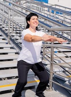 Mulher sênior sorridente fazendo agachamentos ao ar livre