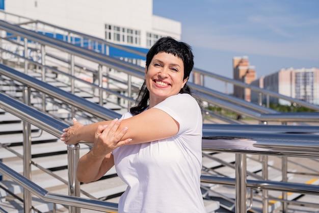 Mulher sênior sorridente fazendo alongamento ao ar livre na cena urbana