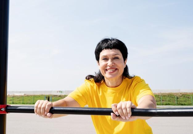 Mulher sênior sorridente fazendo flexões ao ar livre