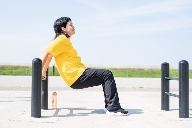 Mulher sênior sorridente fazendo flexões reversas ao ar livre nas barras do campo de esportes