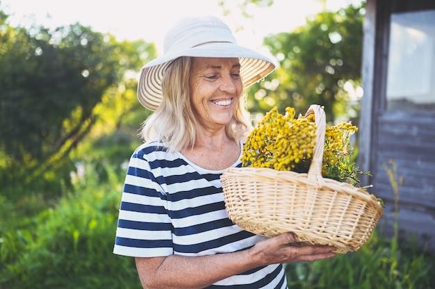 Mulher sênior sorridente feliz posando no jardim de verão com cesta de flores e chapéu de palha.