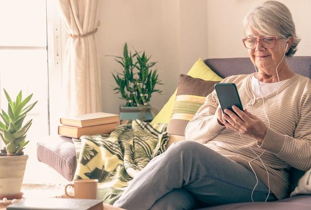 Mulher sênior sorridente relaxando no sofá em casa ouvindo música com o telefone celular. usando fones de ouvido e óculos