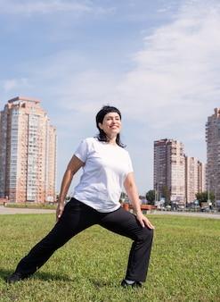 Mulher sênior sorridente se aquecendo, alongando-se ao ar livre no parque