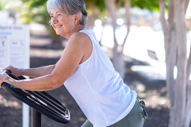 Mulher sênior sorridente se exercitando em um equipamento de playground para ginástica ao ar livre