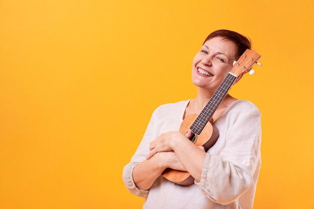 Mulher senior sorridente segurando ukulele
