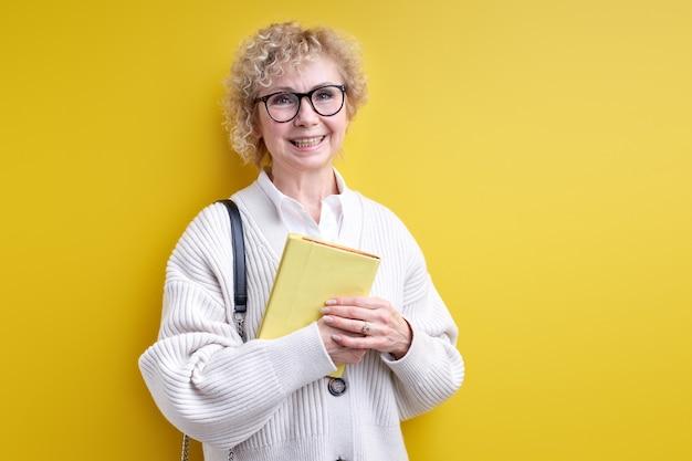 Mulher sênior sorridente segurando um livro nas mãos, usando óculos, professora confiante pronta para ensiná-lo, tutor experiente posando isolado