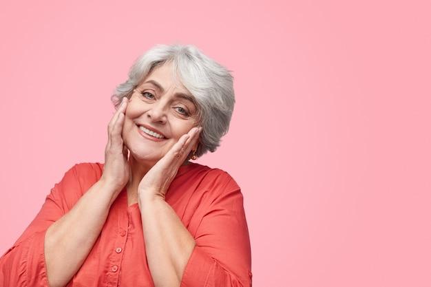 Mulher sênior sorridente tocando a pele