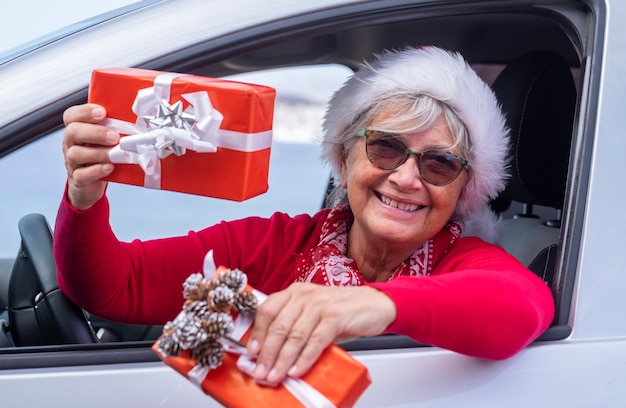 Mulher sênior sorridente vestida de vermelho se inclina para fora da janela do carro usando um chapéu de natal e segurando presentes de natal