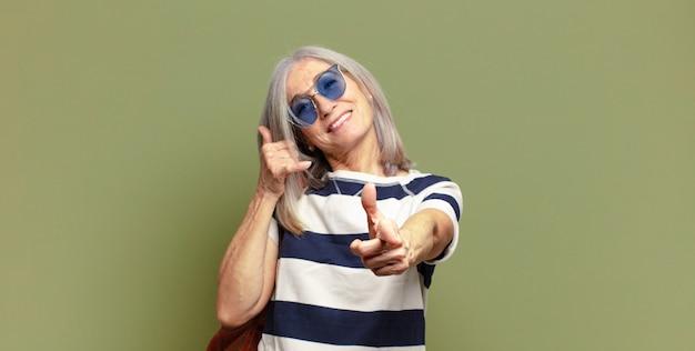 Mulher sênior sorrindo alegremente e apontando para a câmera enquanto faz um gesto para ligar para você, falando ao telefone