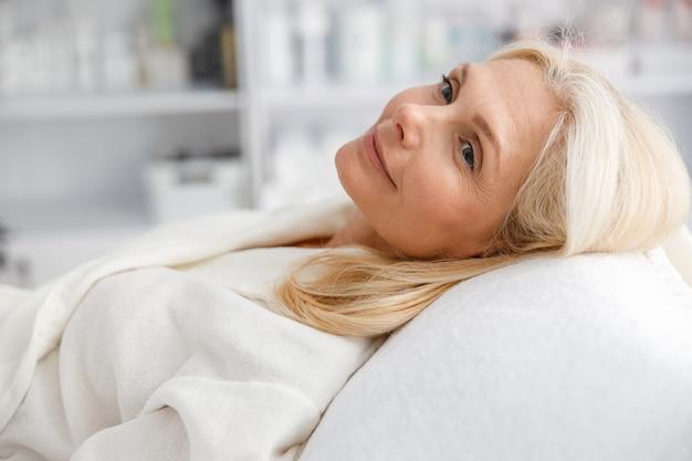 Mulher sênior, sorrindo e esperando o procedimento cosmético na clínica de cosmetologia estética.