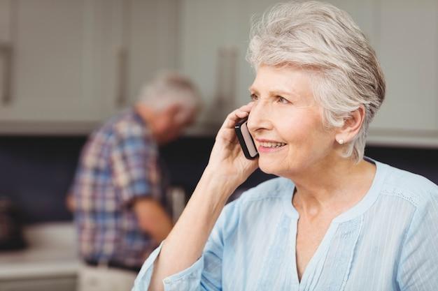 Mulher sênior, sorrindo, enquanto, falando telefone