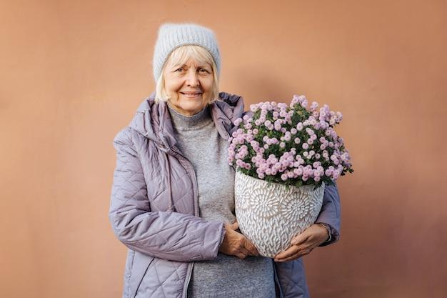 Mulher sênior sorrindo para a câmera e carregando flores em vasos enquanto representa o hobby