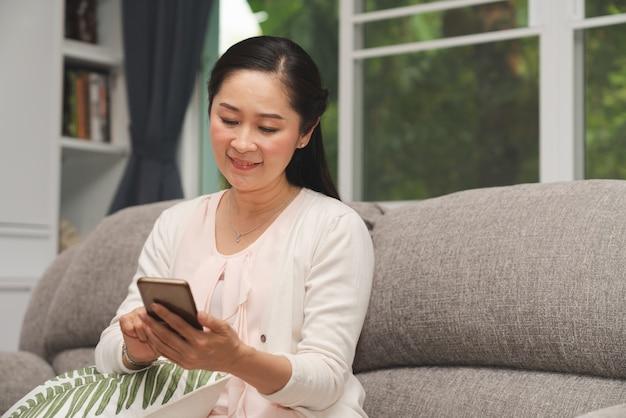 Mulher sênior sorrir enquanto procura smartphone no sofá na sala de estar em casa