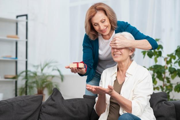 Mulher sênior surpreendendo sua amiga