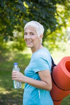 Mulher sênior tem esteira de fitness nas costas no parque