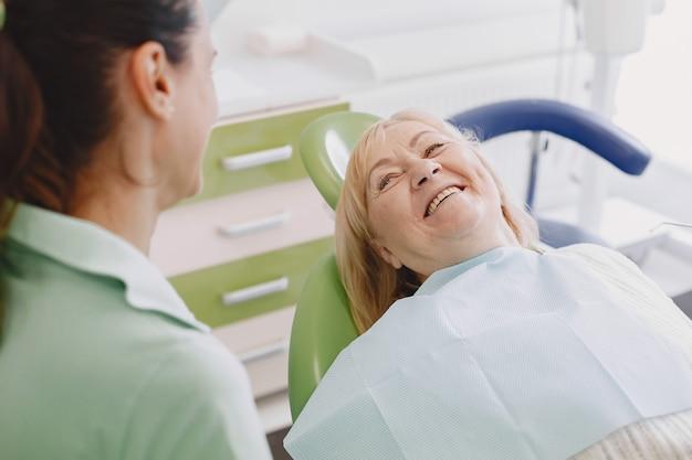Mulher sênior, tendo tratamento dentário no consultório do dentista. mulher está sendo tratada para dentes