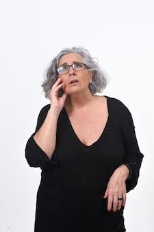 Mulher sênior, tendo uma dúvida ou pergunta sobre fundo branco