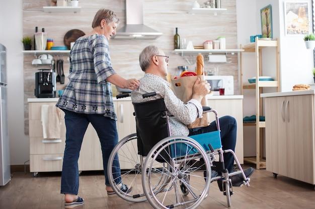 Mulher sênior tirando o saco de papel do marido deficiente em cadeira de rodas. pessoas maduras com legumes frescos do mercado. viver com pessoa com deficiência com deficiência motora