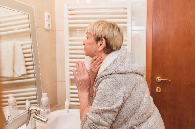Mulher sênior tocando sua pele macia e massagem