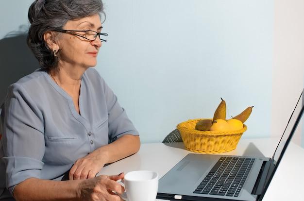 Mulher sênior tomando café e conversando com alguém online no laptop em casa. conceito de videochamada, novo normal, auto-isolamento