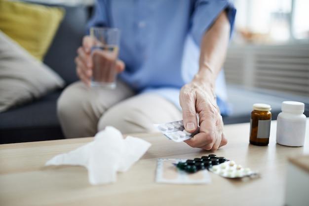 Mulher sênior tomando pílulas closeup