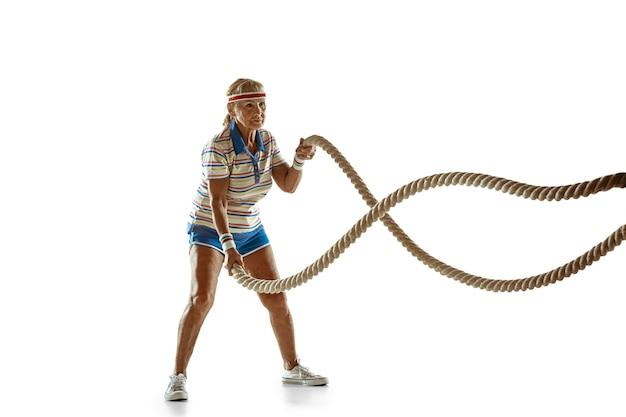 Mulher sênior treinando com cordas em roupas esportivas em fundo branco