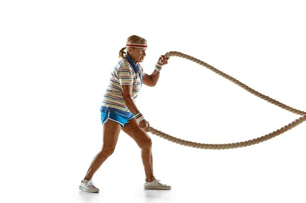 Mulher sênior treinando com cordas em roupas esportivas na parede branca