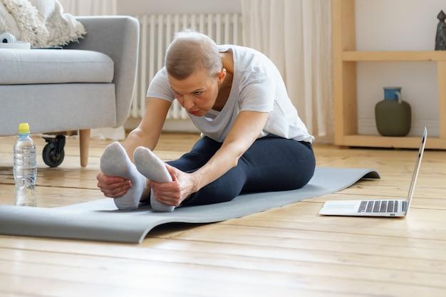 Mulher sênior treinando em casa com seu laptop
