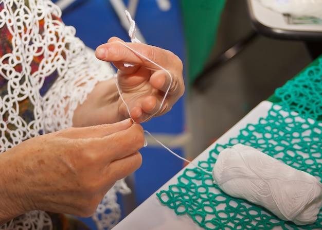 Mulher sênior tricô xale de renda em casa