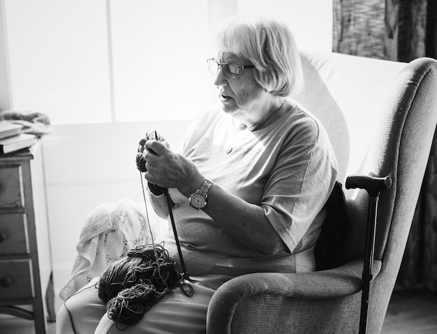 Mulher sênior, tricotando, casa