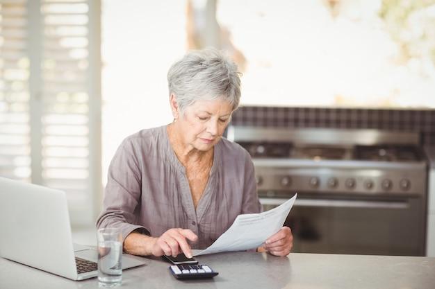 Mulher sênior, usando calculadora, enquanto segura, documento