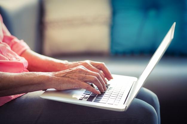 Mulher sênior, usando computador portátil