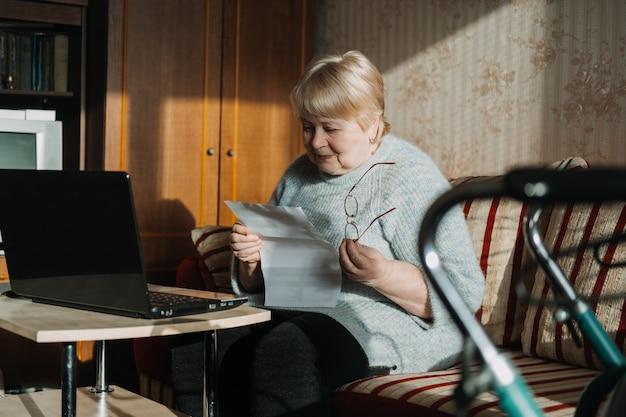 Mulher sênior usando laptop e segurando documentos em casa. focada mulher idosa madura usando computador trabalhando com empréstimos bancários de finanças ou documentos de hipoteca online.
