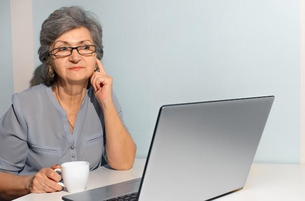 Mulher sênior usando laptop, sonhadoramente olhando para o lado. conceito de videochamada, novo normal, auto-isolamento